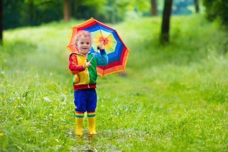 lluvia: Niño jugando en el parque de verano lluvioso. Niño con paraguas de colores del arco iris, capa impermeable y botas salta en el charco de barro y bajo la lluvia. Kid pie en la ducha otoño. diversión al aire libre por cualquier clima