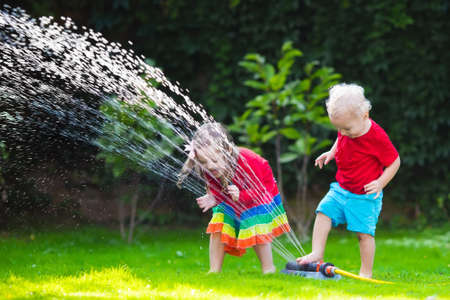 fun day: Child playing with garden sprinkler. Preschooler kid running and jumping. Summer outdoor water fun in the backyard. Children play with hose watering flowers. Kids run and splash on hot sunny day.