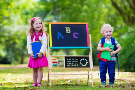 abc kids: Children happy to be back to school. Preschooler girl and boy with backpack and books at black chalk board learning to write letters and read. Kids at preschool or kindergarten learn the alphabet. Stock Photo