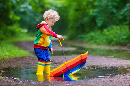 Little boy playing in rainy summer park. Child with colorful rainbow umbrella, waterproof coat and boots jumping in puddle and mud in the rain. Kid walking in autumn shower. Outdoor fun by any weather 版權商用圖片