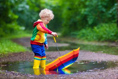 Niño jugando en el parque de verano lluvioso. Niño con paraguas de colores del arco iris, capa impermeable y botas salta en el charco de barro y bajo la lluvia. Kid pie en la ducha otoño. diversión al aire libre por cualquier clima