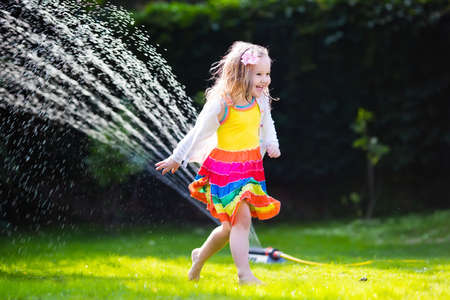 wet girl: Child playing with garden sprinkler. Preschooler kid running and jumping. Summer outdoor water fun in the backyard. Children play with hose watering flowers. Kids run and splash on hot sunny day.