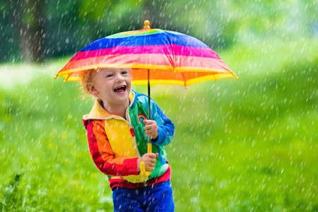 Niño jugando en el parque de verano lluvioso. Niño con paraguas de colores del arco iris, capa impermeable y botas salta en el charco de barro y bajo la lluvia. Kid pie en la ducha otoño. diversión al aire libre por cualquier clima Foto de archivo - 57722856