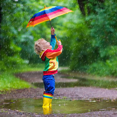 Little boy playing in rainy summer park. Child with colorful rainbow umbrella, waterproof coat and boots jumping in puddle and mud in the rain. Kid walking in autumn shower. Outdoor fun by any weather Standard-Bild
