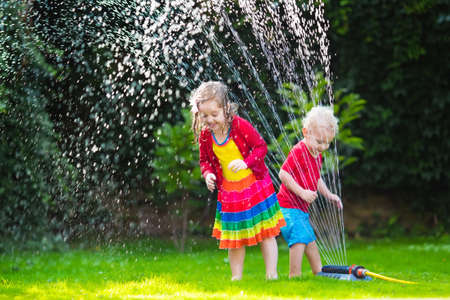 fountain: Child playing with garden sprinkler. Preschooler kid running and jumping. Summer outdoor water fun in the backyard. Children play with hose watering flowers. Kids run and splash on hot sunny day.