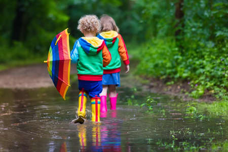 Little boy and girl play in rainy summer park. Children with colorful rainbow umbrella, waterproof boots jump in puddle and mud in the rain. Kids walk in autumn shower. Outdoor fun by any weather