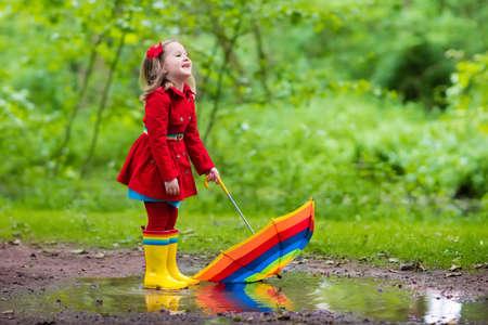 Niña que juega en el parque de verano lluvioso. Niño con paraguas de colores del arco iris, capa impermeable y botas salta en el charco en la lluvia. Kid pie en la ducha otoño. diversión al aire libre por cualquier clima