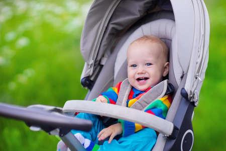 Babyjongen in warme kleurrijke gebreide jasjezitting in moderne wandelwagen op een gang in een park. Kind in buggy. Klein kind in een kinderwagen. Reizen met jonge kinderen. Vervoer voor gezin met baby.