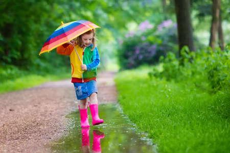 lluvia: Niña que juega en el parque de verano lluvioso. Niño con paraguas de colores del arco iris, capa impermeable, botas salta en el charco de barro y bajo la lluvia. Kid pie en la ducha otoño. diversión al aire libre por cualquier clima