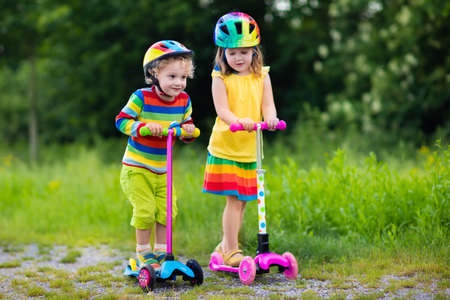 preschoolers: Little boy and girl in safety helmets with scooters. Child learning to ride a scooter in a park. Preschoolers riding a kick board. Kids play outdoors. Active leisure and outdoor sport for children.
