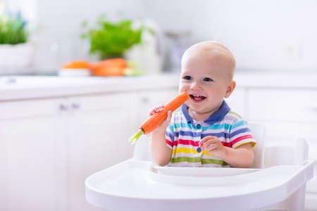 bébé heureux assis dans la chaise haute de manger la carotte dans une cuisine blanche. Une alimentation saine pour les enfants. Bio carotte premier aliment solide pour nourrisson. Les enfants mangent des légumes. Petit garçon mordant légume cru.