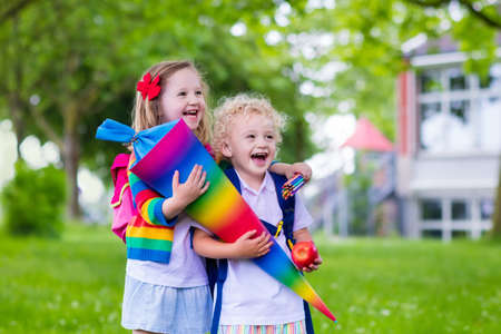 first day: Child going to school. Boy and girl holding traditional candy cone on the first school day. Little students with books excited to be back to school. Beginning of class in Germany with sweets for kids. Stock Photo