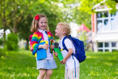 子供は学校に行きます。男の子と女の子の学校初日に本と鉛筆を保持します。小さい学生が学校に戻ることに興奮しています。休暇の後クラスの先