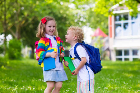 abc kids: Child going to school. Boy and girl holding books and pencils on the first school day. Little students excited to be back to school. Beginning of class after vacation. Kids eating apple in school yard