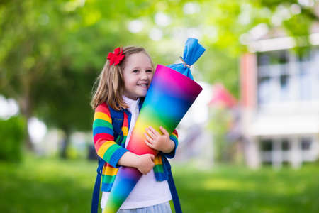 abc kids: Happy child holding traditional German candy cone on the first school day. Little student with backpack and books excited to be back to school. Beginning of class in Germany with sweets for kids. Stock Photo