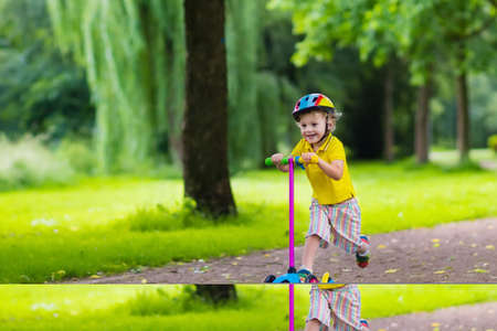 preschooler: Little child learning to ride a scooter in a city park on sunny summer day. Cute preschooler boy in safety helmet riding a roller. Kids play outdoors. Active leisure and outdoor sport for children. Stock Photo