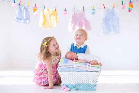 woman bath: Newborn child on a pile of clean dry towels. Brother and sister kissing little sibling. Siblings bonding. Twin toddler kids kiss baby boy. New born kid after bath in a towel. Family washing clothes. Stock Photo