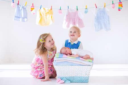 gemelos niÑo y niÑa: niño recién nacido en una pila de toallas limpias y secas. Hermano y hermana besando pequeño hermano. Los hermanos de unión. niños del gemelo del niño besan bebé. Nuevo niño nacido después del baño con una toalla. lavar la ropa de la familia.