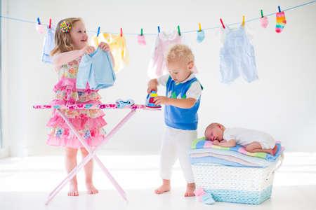 Neugeborenes Kind auf Stapel der sauberen, trockenen Handtücher. Bruder und Schwester spielen mit kleine Geschwister. Geschwister Verklebung. Kinder Bügeln der Wäsche. Twin Kinder spielen mit Baby boy. Neugeborenes Kind nach dem Bad in ein Handtuch