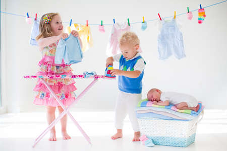 Nowo narodzone dziecko na stos suchych i czystych ręczników. Brat i siostra gra z małego rodzeństwa. Rodzeństwo klejenia. Dzieci prasowania odzieży. Twin dzieci grają z baby boy. Nowy urodzony dziecko po kąpieli w ręcznik