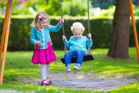 Piccolo ragazzo e ragazza in un parco giochi. Bambino che gioca all'aperto in estate. I bambini giocano in cortile della scuola. Bambino felice all'asilo o scuola materna. I bambini divertirsi a parco giochi all'asilo. Bambino su un'altalena.