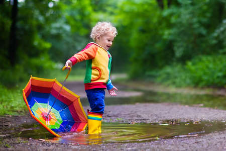 Ragazzino che gioca nella sosta di estate piovosa. Bambino con l'ombrello variopinto arcobaleno, cappotto impermeabile e stivali saltando in pozzanghera di fango e sotto la pioggia. Kid a piedi in autunno doccia. divertimento all'aria aperta con qualsiasi condizione atmosferica