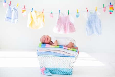 Bebé recién nacido en una pila de toallas limpias y secas. Nueva niño nacido después del baño en una toalla. Lavar la ropa de la familia. Niños desgaste colgando de una línea. Ropa infantil, textil para los niños. Muchacho sonriente después de la ducha.