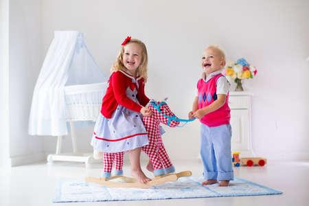 Dos niños juegan en el interior. Niños montar juguete caballito de madera. Niño y niña jugando en la guardería o jardín de infancia. Hermosa guardería para el bebé y niño pequeño. Juguetes para niños de preescolar. Hermano y hermana en casa