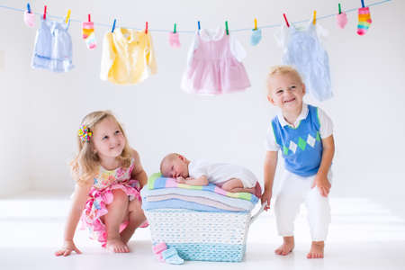 child bath: Newborn child on a pile of clean dry towels. Brother and sister kissing little sibling. Siblings bonding. Twin toddler kids kiss baby boy. New born kid after bath in a towel. Family washing clothes. Stock Photo