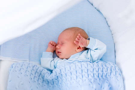 baby bed: Newborn baby boy in bed. New born child sleeping under a blue knitted blanket. Children sleep. Bedding for kids. Infant napping in bed. Healthy little kid shortly after birth. Cable knit textile.