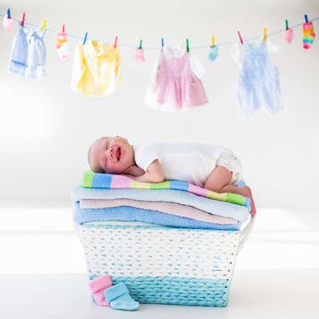 生まれたばかりの赤ちゃんは、きれいな乾いたタオルの山の上。タオルでお風呂の後の新しい生まれの子。家族洗濯。子供服の行にぶら下がってい