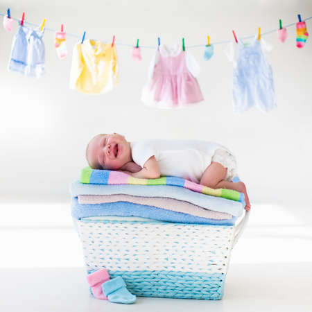 Newborn baby on a pile of clean dry towels. New born child after bath in a towel. Family washing clothes. Kids wear hanging on a line. Infant apparel, textile for children. Smiling boy after shower. Banque d'images