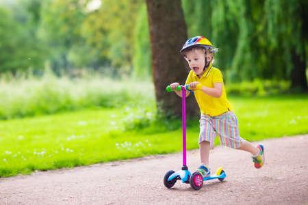 Piccolo bambino che impara a guidare uno scooter in un parco cittadino sulla soleggiata giornata estiva. Ragazzo sveglio del bambino in età prescolare nel casco di sicurezza che guida un rullo. I bambini giocano all'aperto. Tempo libero attivo e sport all'aperto per bambini.