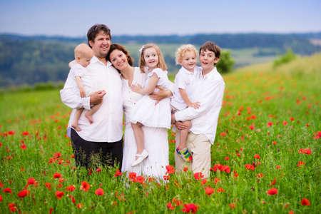 madre e hijo: gran familia con cuatro niños en campo de flor de amapola roja. Madre, padre, niño chico y chica, hijo adolescente y pequeño bebé caminar en la pradera de verano amapolas de la cosecha. Los niños recogen las flores. Foto de archivo