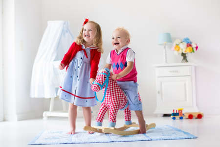 kids toys: Two children play indoors. Kids riding toy rocking horse. Boy and girl playing at day care or kindergarten. Beautiful nursery for baby and toddler. Toys for preschool child. Brother and sister at home