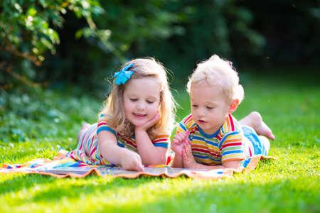 gemelos niÑo y niÑa: Niños que leen un libro en el jardín de verano. Estudio de niños. Juego del muchacho y de la muchacha en el patio de la escuela. Amigos en edad preescolar juegan y aprenden. Hermanos hacer la tarea. Niño de Kindergarten y niños pequeños leen libros.