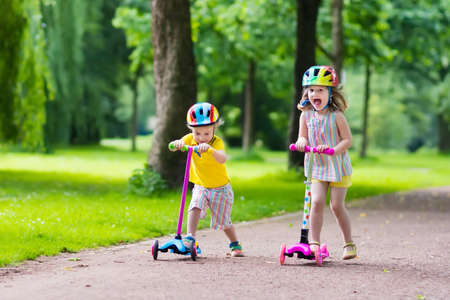 scooters: Children learn to ride scooter in a park on sunny summer day. Preschooler boy and girl in safety helmet riding a roller. Kids play outdoors with scooters. Active leisure and outdoor sport for child.