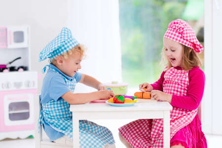 preschooler: Little girl and boy in chef hat and apron cooking in toy kitchen. Educational toys for young children. Kids play, cut wooden vegetables and cook. Toddler kid playing with stove, pans and dishes. Stock Photo