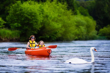river: Family on kayaks and canoe tour. Mother and child paddling in kayak in a river on a sunny day. Children in summer sport camp. Active preschooler kayaking in a lake. Water fun during school vacation.