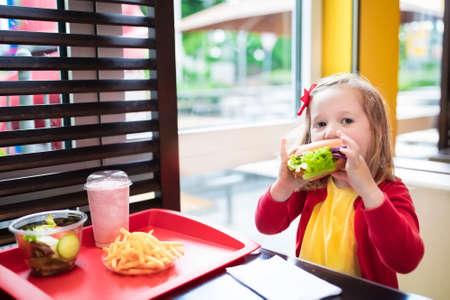 niños comiendo: Niña que come la hamburguesa y papas fritas en un restaurante de comida rápida. Niño que tiene chips de sándwich y papas para el almuerzo. Los niños comen alimentos poco saludables de grasa. Sándwich de comida rápida para los niños. Foto de archivo