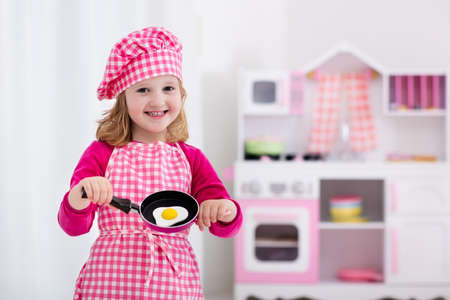 Bambina in cappello da chef e grembiule da cucina uova fritte nella cucina giocattolo. Giocattoli in legno per i bambini. I bambini giocano e cucinare a casa o all'asilo. Bambino bambino che gioca con fornelli, stoviglie, pentole e stoviglie.