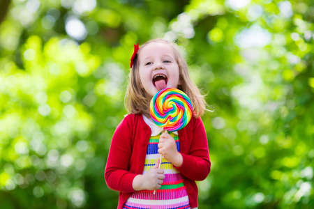 preschooler: Cute little girl with big colorful lollipop. Child eating sweet candy bar. Sweets for young kids. Summer outdoor fun. Preschooler kid with sugar lolly. Children having snack in a park after preschool.