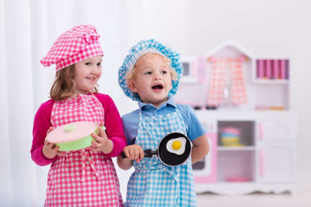 juguetes de madera: Little girl and boy in chef hat and apron cooking fried eggs in toy kitchen.  Wooden toys for young children. Kids play and cook at home or daycare. Toddler kid playing with stove, pans and dishes.