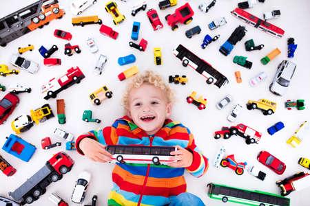 床に横たわってモデル車のコレクションで遊んで面白い中幼児少年。子供のおもちゃを輸送、救助。子供部屋のおもちゃ混乱。上からの眺め。小さ