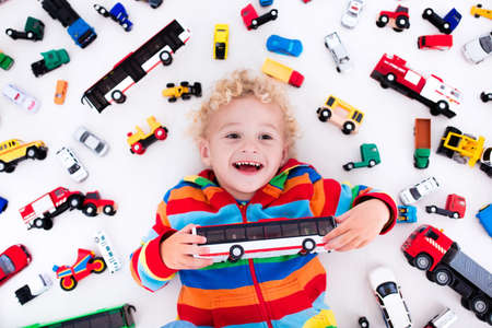 toy truck: Funny curly toddler boy playing with his model car collection lying on the floor. Transportation and rescue toys for children. Toy mess in kids room. View from above. Many cars for little boys.
