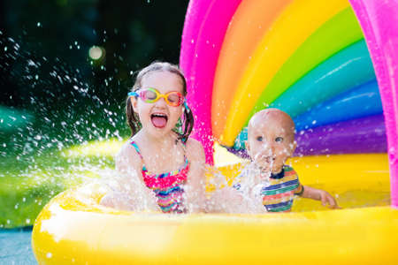 Children playing in inflatable baby pool. Kids swim and splash in colorful garden play center. Happy boy and girl playing with water toys on hot summer day. Family having fun outdoors in the backyard. Stockfoto