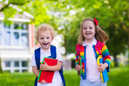Child going to school. Boy and girl holding books and pencils on the first school day. Little students excited to be back to school. Beginning of class after vacation. Kids eating apple in school yard
