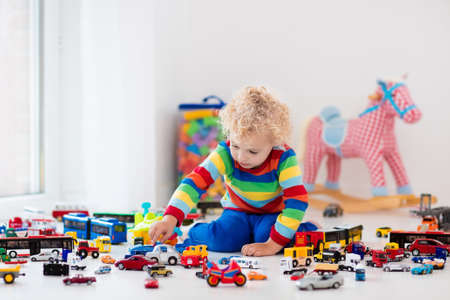 Funny curly toddler boy playing with his model car collection on the floor. Transportation and rescue toys for children. Toy mess in child room. Many cars for little boys. Educational games for kids. Stock Photo