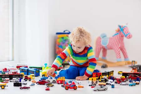 Grappige krullende peuter jongen speelt met zijn model auto collectie op de vloer. Transport en redding speelgoed voor kinderen. Toy puinhoop in kinderkamer. Veel auto's voor kleine jongens. Educatieve spelletjes voor kinderen. Stockfoto