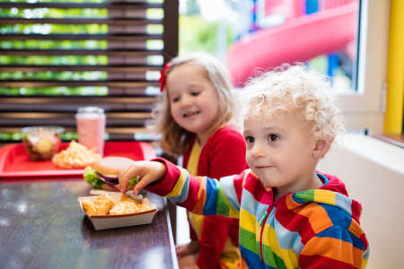 fried food: Little girl and boy eating chicken nuggets, hamburger and French fries in a fast food restaurant. Child with sandwich and potato chips. Kids eat unhealthy fat food. Fastfood sandwich for children.
